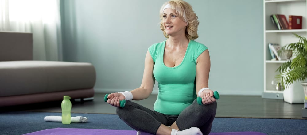 sportive middle aged woman holding dumbbells sitting on mat home exercises